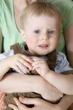 Las manos del `s de la madre abrazan a su pequeño bebé serio foto de archivo