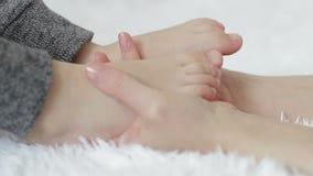 Las manos del ` s de la madre tocan el primer de las piernas del ` s del niño almacen de metraje de vídeo