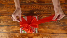 Las manos del ` s de la muchacha están abriendo la caja de regalo con la cinta roja, visión superior, cámara lenta metrajes