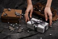 Las manos del ` s de la muchacha pusieron la caja de regalo en la tabla Fondo de la decoración de la Navidad fotografía de archivo libre de regalías
