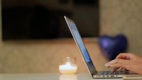 Las manos del ` s de la mujer crean el poema en el ordenador portátil Imagen de archivo libre de regalías