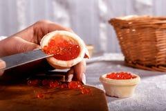 Las manos del ` s de la mujer llenan un tartlet del caviar rojo mediante un cuchillo Foto de archivo libre de regalías