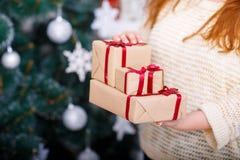Las manos del ` s de la mujer llevan a cabo un Año Nuevo presente en el fondo de un árbol de navidad Fotografía de archivo