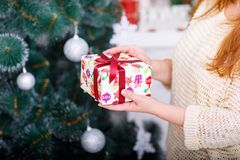 Las manos del ` s de la mujer llevan a cabo un Año Nuevo presente en el fondo de un árbol de navidad Fotografía de archivo libre de regalías