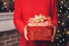 Las manos del ` s de la mujer que llevaban a cabo la Navidad o el Año Nuevo adornaron la caja de regalo Imagenes de archivo