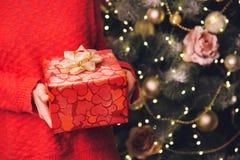 Las manos del ` s de la mujer que llevaban a cabo la Navidad o el Año Nuevo adornaron la caja de regalo Imagen de archivo libre de regalías