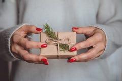 Las manos del ` s de la mujer sostienen la caja adornada de la Navidad o de regalo del Año Nuevo tonelada Fotografía de archivo