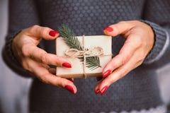 Las manos del ` s de la mujer sostienen la caja adornada de la Navidad o de regalo del Año Nuevo tonelada Imagenes de archivo