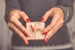 Las manos del ` s de la mujer sostienen la caja adornada de la Navidad o de regalo del Año Nuevo tonelada Fotografía de archivo libre de regalías