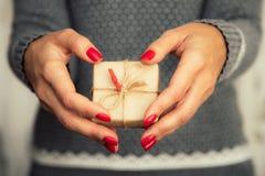Las manos del ` s de la mujer sostienen la caja adornada de la Navidad o de regalo del Año Nuevo tonelada Foto de archivo libre de regalías
