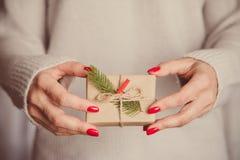 Las manos del ` s de la mujer sostienen la caja adornada de la Navidad o de regalo del Año Nuevo tonelada Foto de archivo
