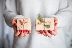 Las manos del ` s de la mujer sostienen la caja adornada de la Navidad o de regalo del Año Nuevo tonelada Imagen de archivo