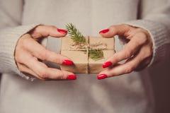 Las manos del ` s de la mujer sostienen la caja adornada de la Navidad o de regalo del Año Nuevo tonelada Imagen de archivo libre de regalías