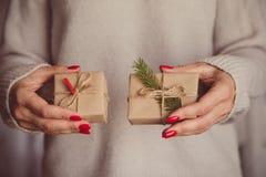 Las manos del ` s de la mujer sostienen la caja adornada de la Navidad o de regalo del Año Nuevo tonelada Fotos de archivo