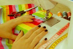 Las manos del ` s de la mujer usando la máquina de coser con los carretes del color roscan fotografía de archivo