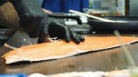Las manos del ` s de los hombres en guantes negros sacan los huesos de los prendederos de pescados ilustración del vector