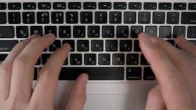 Las manos del ` s de los hombres imprimen en el ordenador portátil, visión superior metrajes