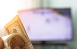Las manos del ` s de los hombres llevan a cabo un paquete de dólares contra la perspectiva de una TV en la cual muestren hockey,  foto de archivo