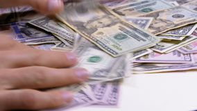 Las manos del ` s de los hombres recogen en los dólares americanos del montón de diversas denominaciones almacen de metraje de vídeo