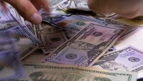 Las manos del ` s de los hombres recogen en los dólares americanos del montón de diversas denominaciones metrajes