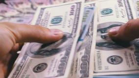Las manos del ` s de los hombres sostienen una pila de dólares americanos contra la perspectiva del dinero giratorio metrajes