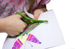 Las manos del ` s de los niños con las tijeras cortaron la mariposa coloreada encendido fotografía de archivo libre de regalías
