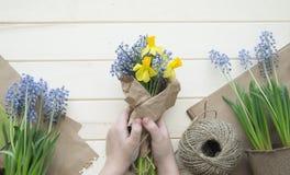 Las manos del ` s de los niños recogen un ramo como regalo Un regalo para la mamá imagenes de archivo