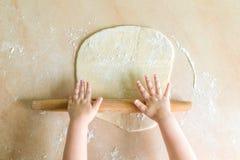 Las manos del ` s de los niños rodaron la pasta Fotos de archivo libres de regalías