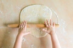 Las manos del ` s de los niños rodaron la pasta Imágenes de archivo libres de regalías