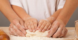 Las manos del ` s de los niños y las manos de su madre y amasan el tog de la pasta Imagen de archivo