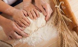 Las manos del ` s de los niños y las manos de su madre y amasan el tog de la pasta Imagen de archivo libre de regalías