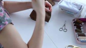 Las manos del ` s de las mujeres crean un producto de materia textil, juguete, modelo almacen de video