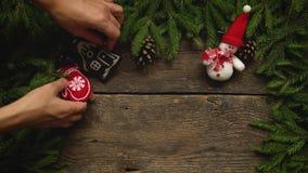 Las manos del ` s de las mujeres crean una decoración de la Navidad Ramas de árbol de navidad con los conos y decoraciones de la  almacen de metraje de vídeo