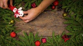 Las manos del ` s de las mujeres crean una decoración de la Navidad Ramas de árbol de navidad con los conos y decoraciones de la  metrajes