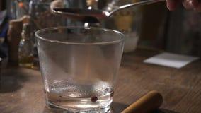 Las manos del ` s de las mujeres vierten el líquido rojo de una cuchara en un vidrio de agua caliente