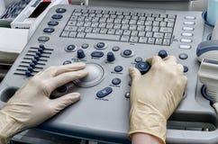 Las manos del ` s del doctor en la máquina del ultrasonido Fotografía de archivo libre de regalías