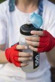 Las manos del ` s del muchacho en guantes de los deportes, guardan una botella de los deportes de agua Imagenes de archivo