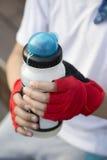Las manos del ` s del muchacho en guantes de los deportes, guardan una botella de los deportes de agua Fotografía de archivo