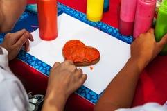 Las manos del ` s del niño adornan las galletas los niños hacen las galletas Foto de archivo