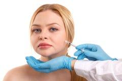 Las manos del ` s del doctor hacen las inyecciones de Botox de una mujer hermosa en el área de la mejilla Aislado imagenes de archivo