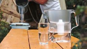 Las manos del ` s del hombre vierten el agua del cubo de bien en el filtro de agua que se coloca en la tabla de madera al aire li almacen de video