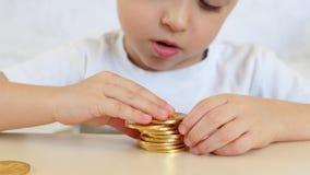 Las manos del ` s del niño están jugando con las monedas de oro de bitcoins en la tabla Los juegos de niños con una moneda crypto almacen de video