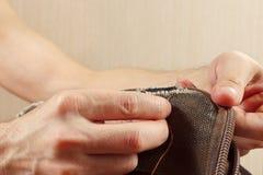 Las manos del sastre cosen el bolso durable del paño con cierre de la aguja para arriba Imagenes de archivo