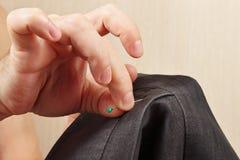 Las manos del sastre fijaron el perno al primer gris de la chaqueta Foto de archivo libre de regalías