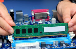 Las manos del técnico que instalan memoria Imagen de archivo