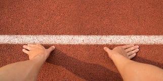 Las manos del tacto de la visión superior a la línea empiezan para correr en pista del atletismo Imágenes de archivo libres de regalías