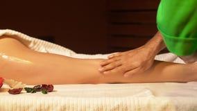 Las manos del terapeuta del masaje vierten el aceite del masaje en la pierna femenina almacen de video