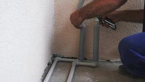 Las manos del trabajador cubren los tubos de agua con la capa del pvc Capa de capa de los tubos y de los cortes del agua del trab almacen de video