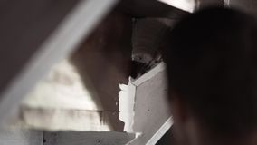 Las manos del trabajador de sexo masculino pintan profesionalmente las paredes grises en blanco con el cepillo grande almacen de video