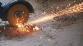 Las manos del trabajador que cortaban el tubo del metal con la circular consideraron con las chispas anaranjadas Concepto de la c metrajes